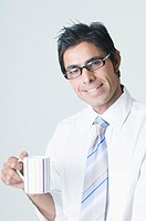 Portrait of a businessman wearing eyeglasses and holding a cup of coffee