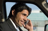 Close-up of a businessman talking on a mobile phone in a car
