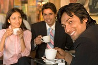 Two businessmen and a businesswoman holding coffee cups