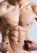 Mid section view of a young man showing his abdominal muscles