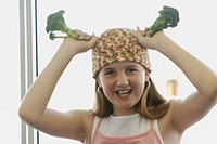 Pre-teen girl holding organic broccoli, wearing shirt made with hemp fibre, Canada, Manitoba, Brandon