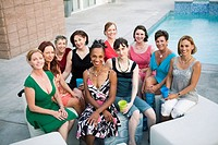 Women smiling together beside swimming pool
