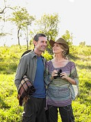 Adult couple outdoors man carrying blanket woman binoculars smiling