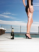 Woman in bathing suit standing with champagne at outdoor pool low section (thumbnail)