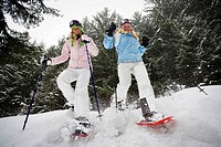 Low angle view of two young blonde women walking down small hill in forest using snow-shoes