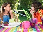 Two girls 10_12 blowing party puffers at birthday party