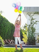 Portrait of girl 10_12 holding bunch of balloons over head