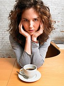 Serious woman looking at camera at desk with coffee cup ,