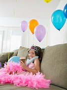 Young girl 7_9 sitting on sofa with balloons eating cupcake