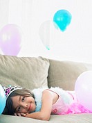 Young girl 7_9 lying on sofa with balloons