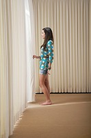 Teenage girl 16_18 standing in empty room drawing aside blinds side view