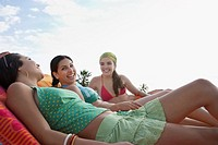 Three teenage girls 16_17 relaxing on sunloungers