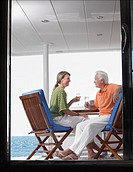 Middle-aged couple drinking wine on yacht profile view through door (thumbnail)