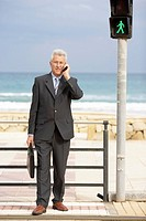Senior businessman using mobile phone at pedestrian crossing