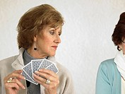 Two senior women playing cards, one looking over shoulder