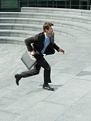 Businessman with briefcase running up steps outdoors side view