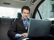 Mid adult businessman sitting at back seat of car using laptop