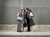 Two businesswomen and two businessmen looking at paper by concrete wall, Alicante, Spain,