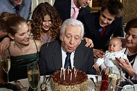 Senior man blowing out candles on cake as family watches
