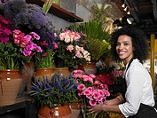 Young female florist holding flowers, smiling, portrait