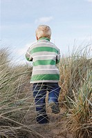 Boy 3_4 walking on path among long grass