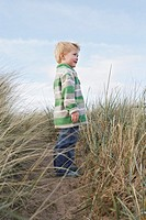 Boy 3_4 standing on path among long grass