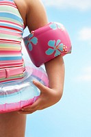 Girl 7_9 years wearing inflatable ring and water wings mid section
