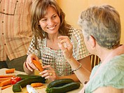 Senior woman making ´ok´ sign, adult daughter preparing food, smiling