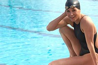 Female swimmer sitting by pool, smiling, portrait