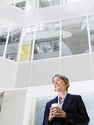 Business woman holding cup of coffee standing in atrium of office building low angle view