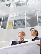 Two business people holding blueprint low angle view