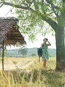 Young woman looking through binoculars by thatched roof