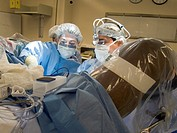 Trauma surgeon wearing a headlight and a surgical resident debriding removing necrotic muscle from the perineum of a male trauma patient in stirrups T...