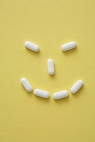 Conceptual image of pills on a yellow background showing a happy face