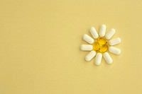 Conceptual image of aspirin pills and omega 3 gelcaps arranged into a flower shape on a pastel yellow background