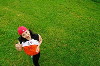 23 Year old Latino Woman (Ecuadorian) smiling and standing on the grass wearing a red hat and two colored t-shirts (orange, black, white) that read, ´...