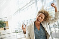 Excited businesswoman holding cell phone