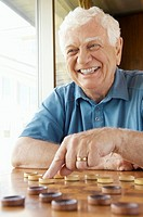 Senior man playing checkers