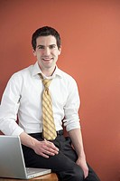 Young businessman sitting on desk