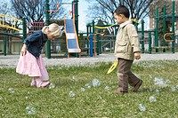 Preschool children making bubbles on playground