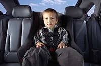 Boy fastened to child car seat