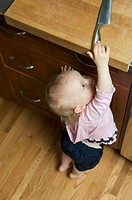 Toddler reaching for knife on kitchen counter