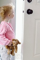 Toddler looking through open door