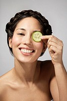Woman with cucumber slice eye treatment