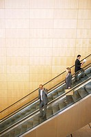 Three businesspeople on escalators