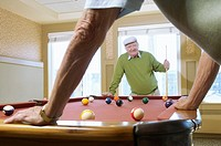 Two senior men playing pool