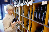 Shopper reading wine labels (thumbnail)