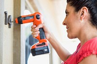 Woman drilling numbers onto house (thumbnail)