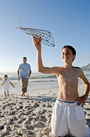 Boy holding a model airplane with his father and sister running on the beach in the background