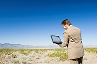 Man with laptop in desert